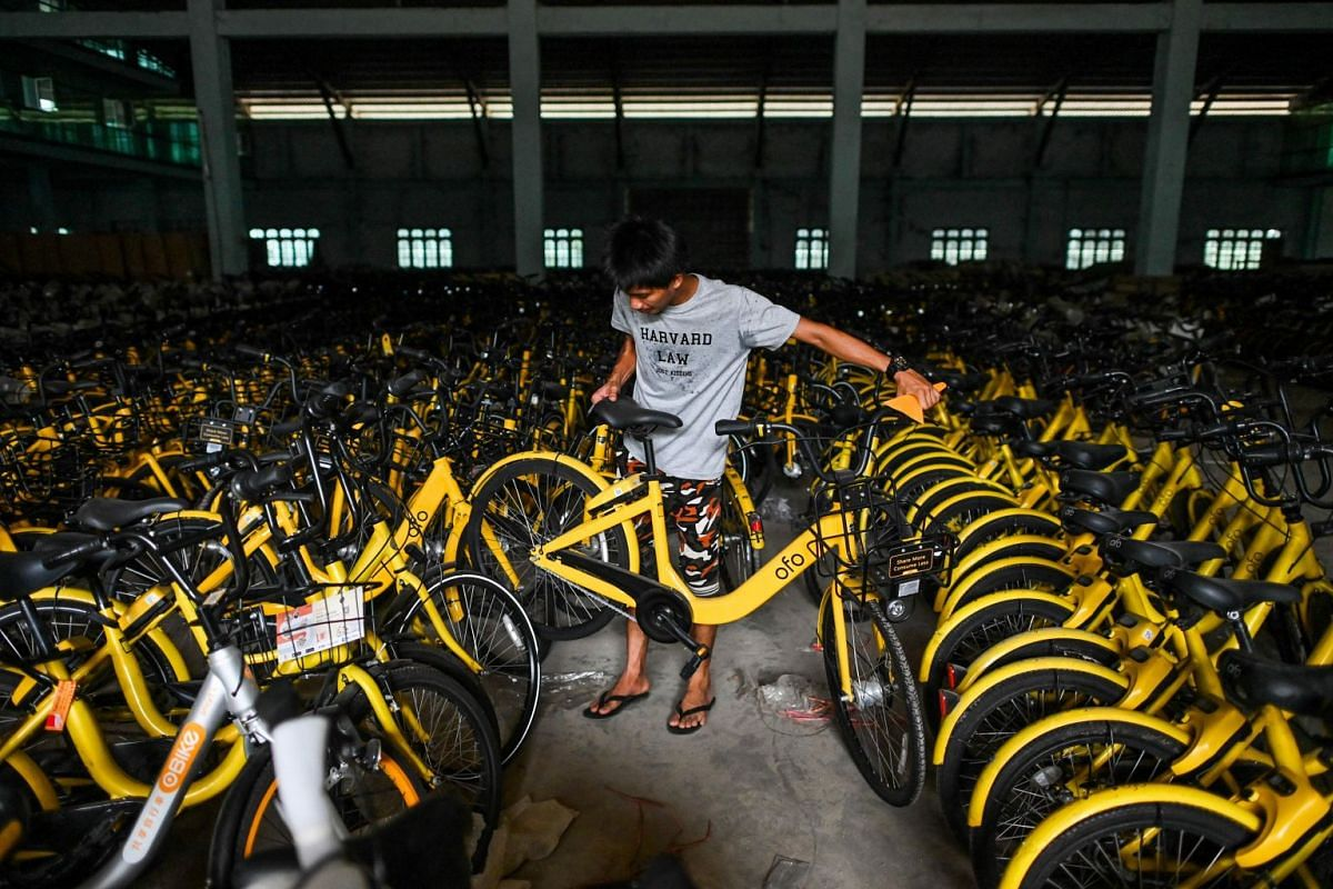 A man arranges bicycles previously used in bike-sharing companies in a warehouse in Yangon, on June 15, 2019.