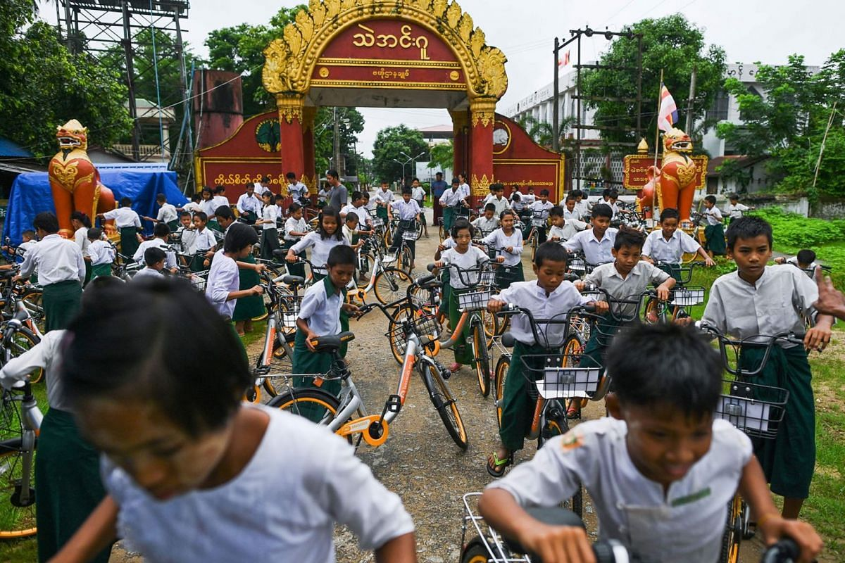 """In this picture taken on June 18, 2019, students ride bicycles, previously used in bike-sharing companies and shipped from Singapore, which have been donated as part of the """"Lesswalk"""" scheme in the compound of a Buddhist monastery on the outskirts of"""