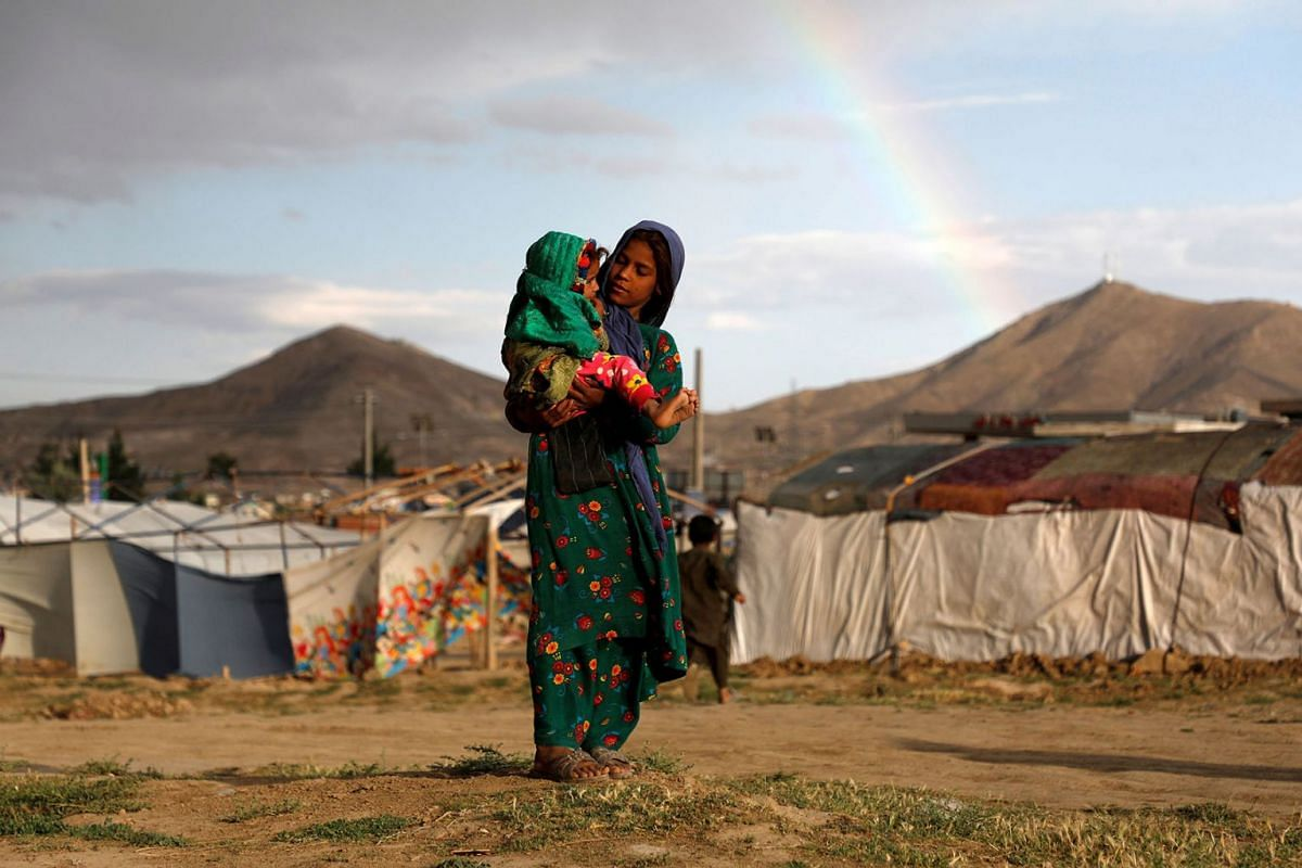 Internally displaced Afghan girl carries a child near their shelter at a refugee camp on the outskirts of Kabul, Afghanistan June 20, 2019. PHOTO: REUTERS