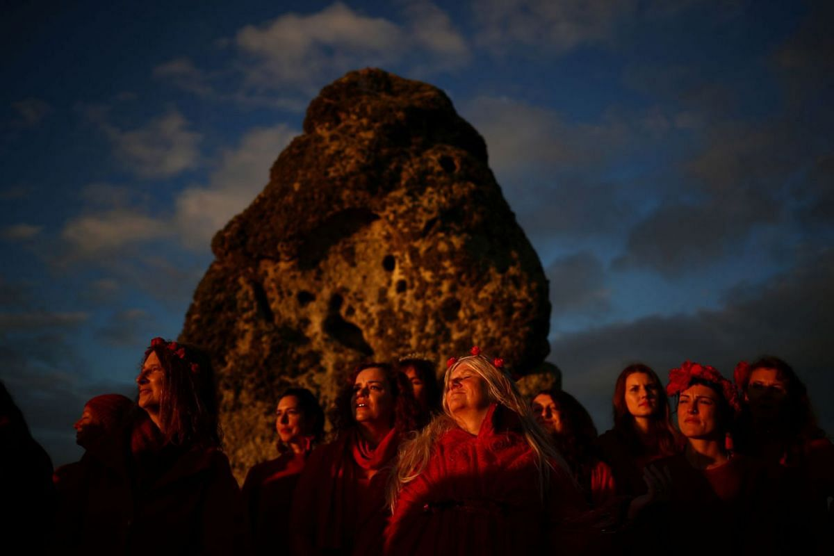 Revellers watch the sun set on the eve of the Summer Solstice at the Stonehenge stone circle, in Amesbury, Britain June 20, 2019. PHOTO: REUTERS