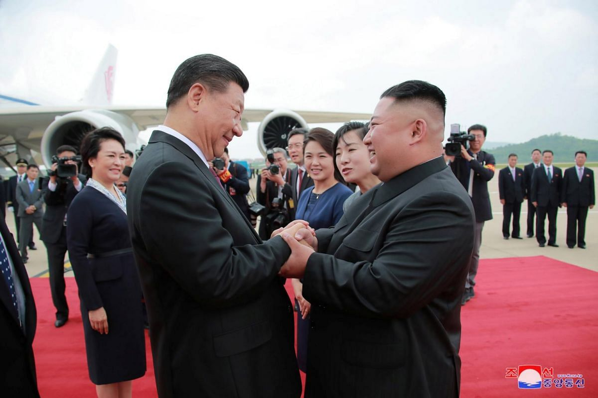 North Korean leader Kim Jong Un welcomes Chinese President Xi Jinping at the Pyongyang International Airport in Pyongyang, North Korea, in this undated photo released on June 21, 2019.