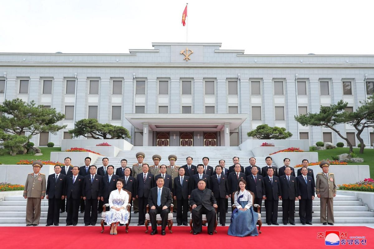 Chinese President Xi Jinping and North Korean leader Kim Jong Un, pose for a group photo with their wives Peng Liyuan and Ri Sol Ju, and North Korean officials in this undated photo released on June 21, 2019.