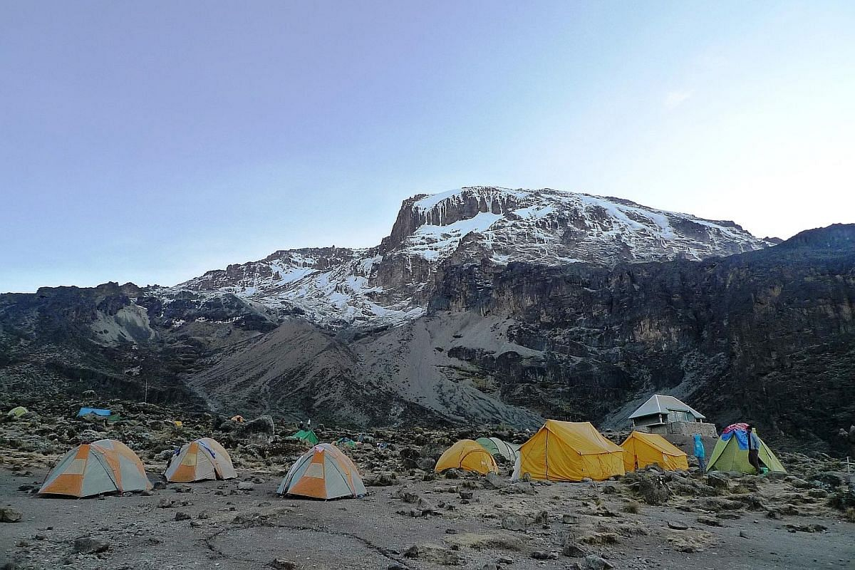 1. Porters gingerly navigate the steep Baranco Wall with over-sized duffle bags of supplies. 2. Tented campsites along the trek offer priceless mountain views and nights under the stars. 3. Mount Kilimanjaro's arctic zone. 4. The monotonous trek acro