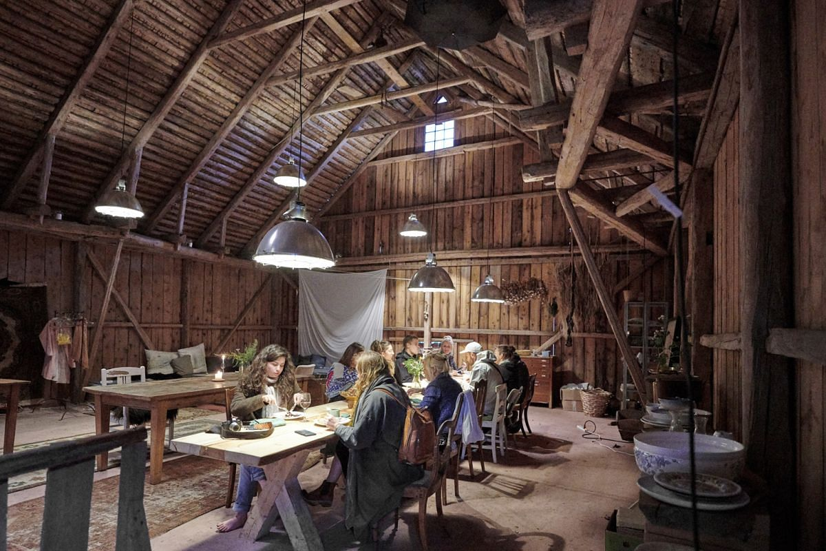 Co-founder Flemming Hansen taking guests through orientation at Stedsans in the Woods and a communal meal in a barn at the nature retreat (above).