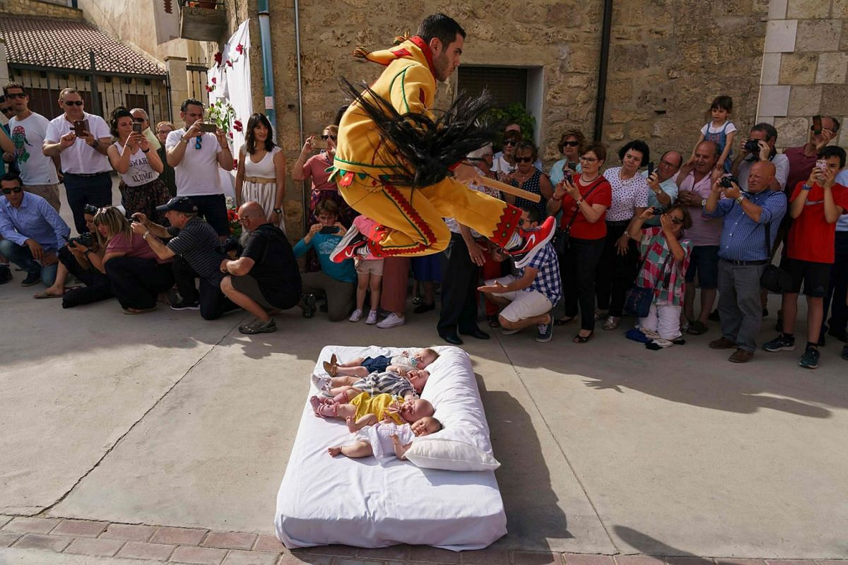 """The """"Colacho"""", a character that represents the devil, jumps over babies lying on a mattress in the street during 'El Salto del Colacho' (The Devil's Jump) baby jumping festival, in the village of Castrillo de Murcia, near Burgos, Spain, on June 23, 2"""