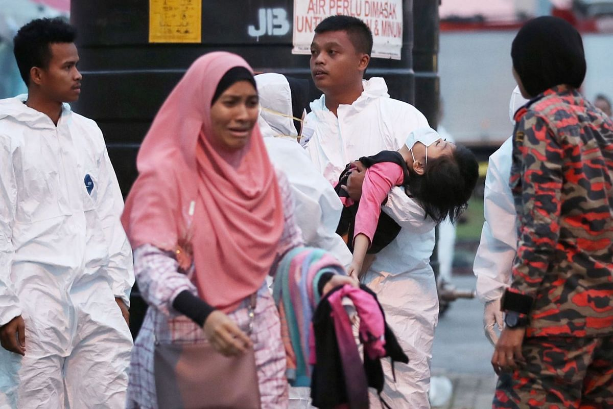 Medical staff transferring a child from a medical tent to a waiting ambulance at the Pasir Gudang Indoor Stadium in Johor accompanied by a worried family member, June 24, 2019. More than 70 students in Johor's Pasir Gudang district were referred to