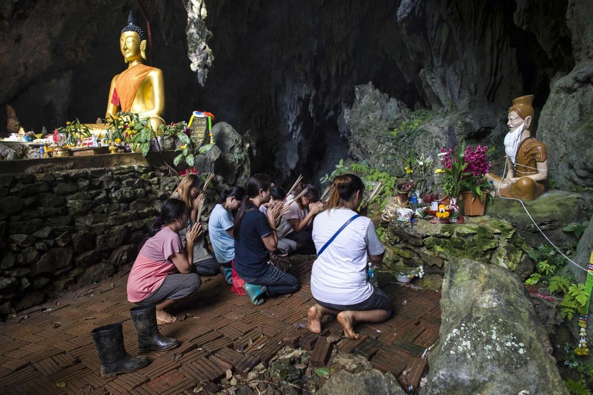 """In this file photo taken on July 5, 2018, family members of the 12 boys and their coach from the """"Wild Boars"""" football team trapped in the Tham Luang cave, pray before a shrine in the cave area as operations were underway to rescue them in the Khun N"""