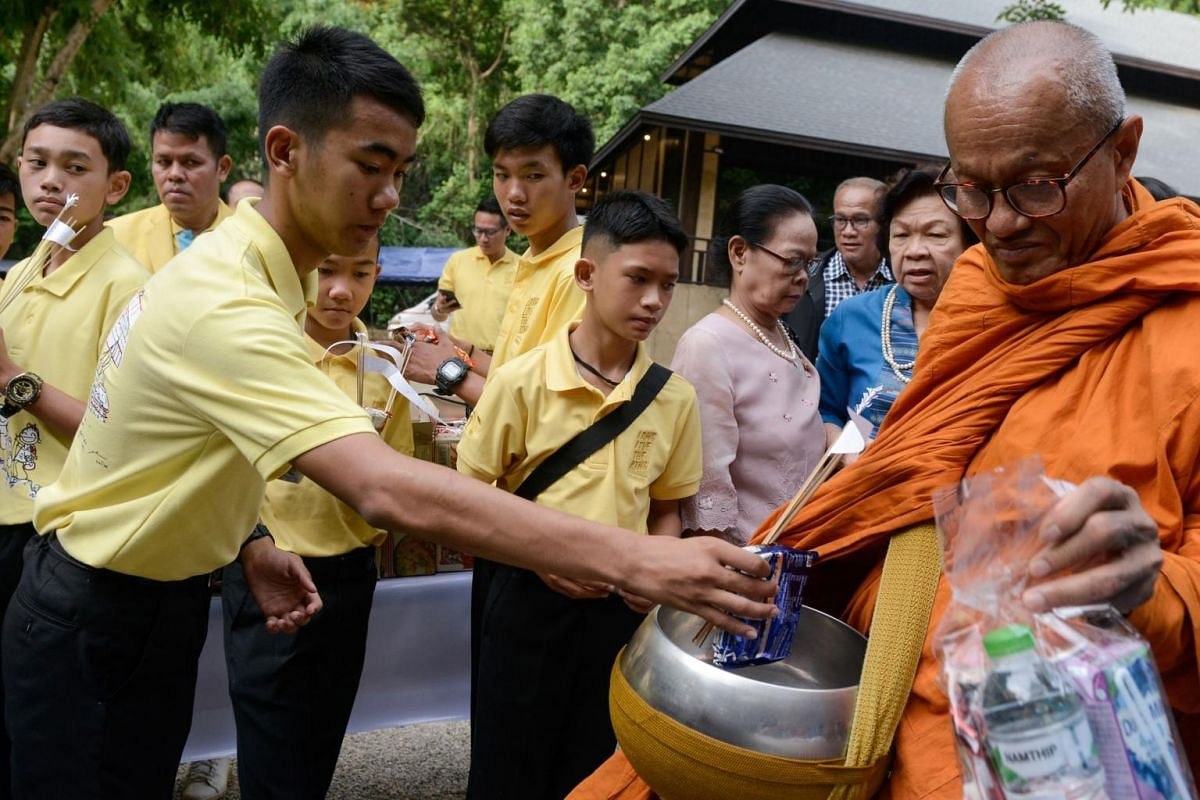Members of the Wild Boars football team offer food to monks as they mark the first anniversary of their rescue from the Tham Luang cave in the Mae Sai district of Chiang Rai province on June 24, 2019.