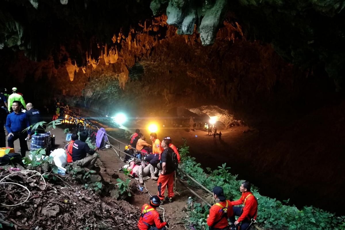 Thai rescue workers and park officials rest outside the Tham Luang Nang Non cave, as the authorities search for 12 football players and their coach who went missing and believed to be trapped in Tham Luang Nang Non cave at Mae Sai district, Chiang Ra
