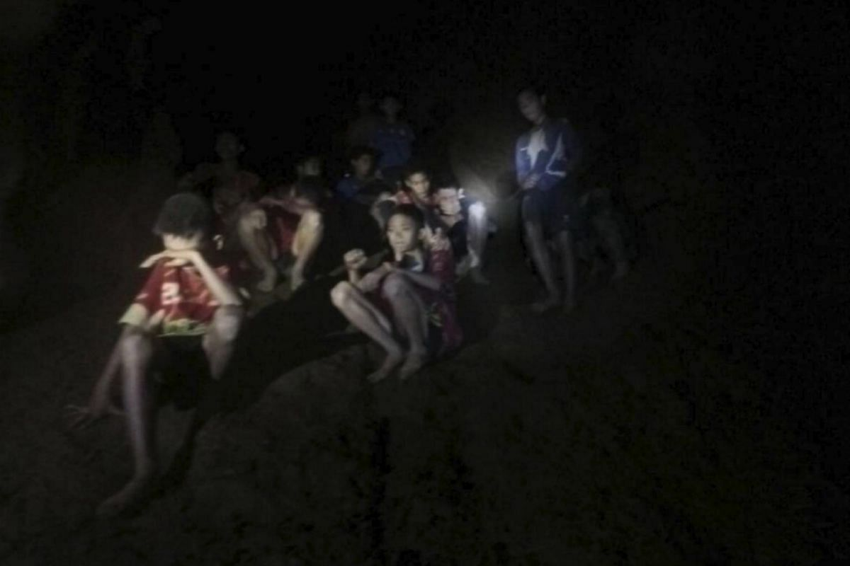 An undated handout photo released by Royal Thai Army shows the missing 13 members of a youth soccer team including their coach, moments after they were found inside the cave complex at Tham Luang cave in Khun Nam Nang Non Forest Park, Chiang Rai prov