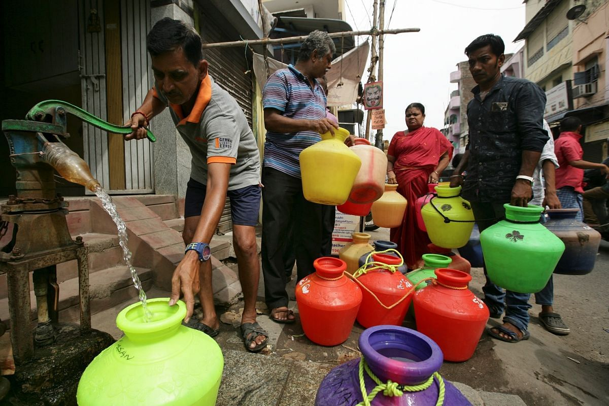 A man using a hand-pump to fill containers with drinking water as others wait in line. Since the water crisis, the Tamil Nadu government has announced measures for restoration of traditional water bodies, including an allocation of 5 million rupees.