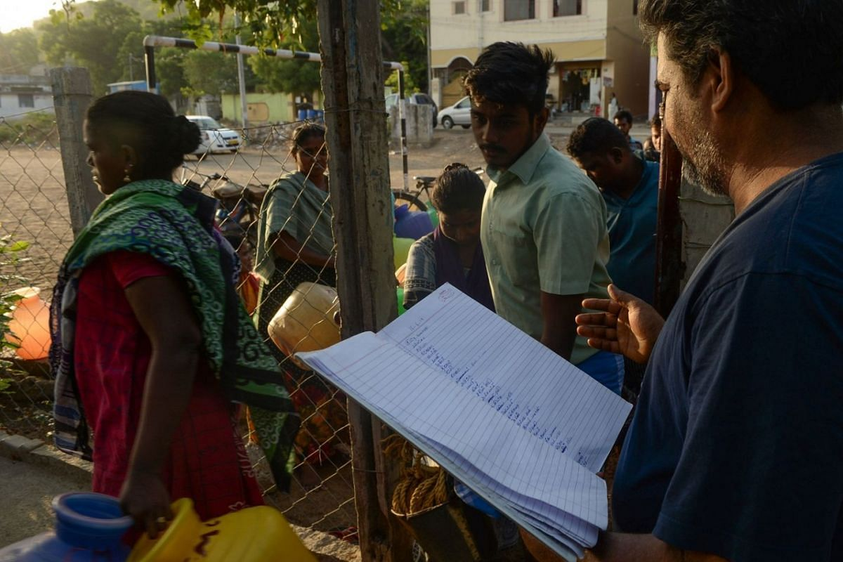 A man checking a list of names of residents who drew lots to collect water from the community well.