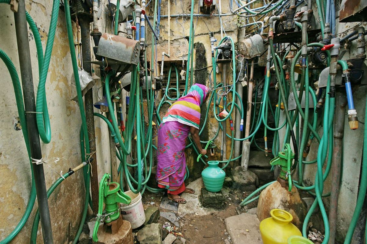 A woman uses a hand pump to fill up a container with drinking water in Chennai, India, June 25, 2019. PHOTO: REUTERS