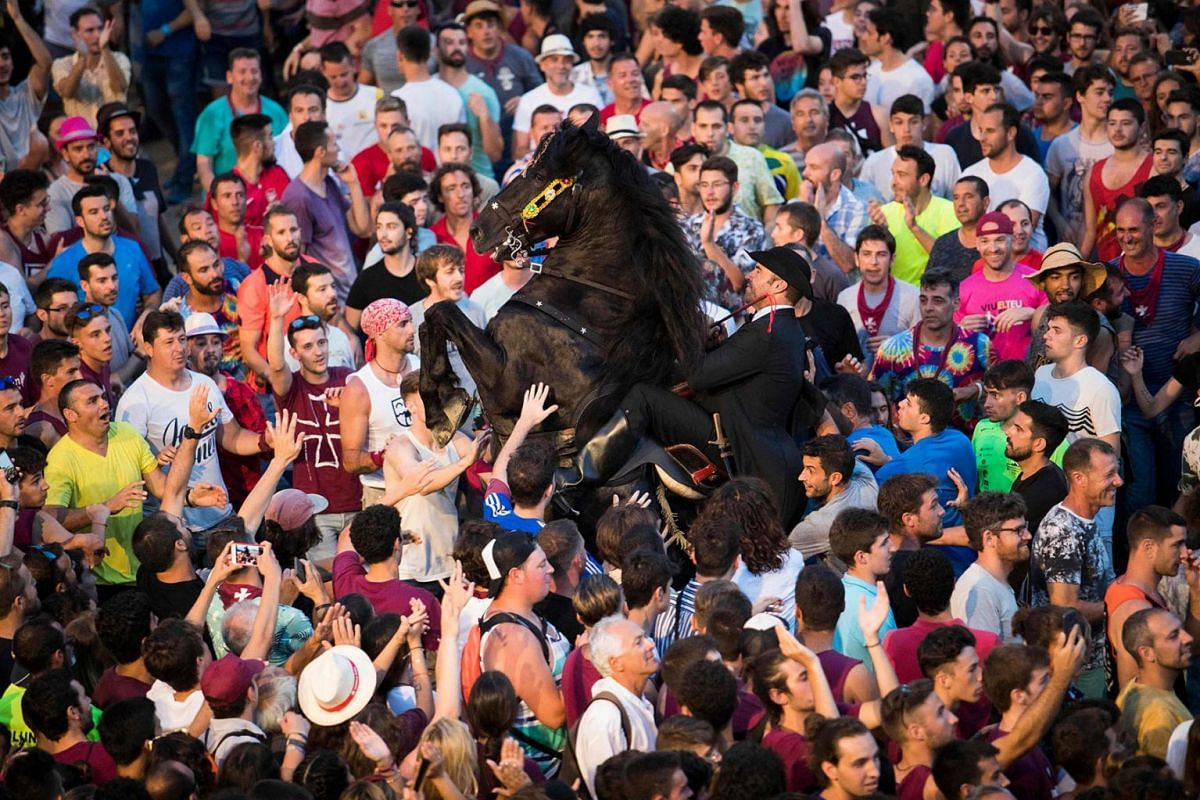 """A horse rears in the crowd during the """"Jocs des Pla"""", equestrian games celebrated at the crowded port during the traditional Sant Joan (Saint John) festival in the town of Ciutadella, on the Balearic Island of Minorca, on Saint John's day on June 24,"""