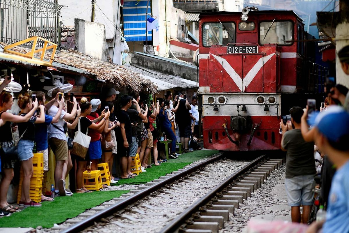 A photo issued on June 26, 2019 shows visitors and tourists standing on the sides to photograph a passing train in Hanoi's popular train street, June 9, 2019. PHOTO: AFP