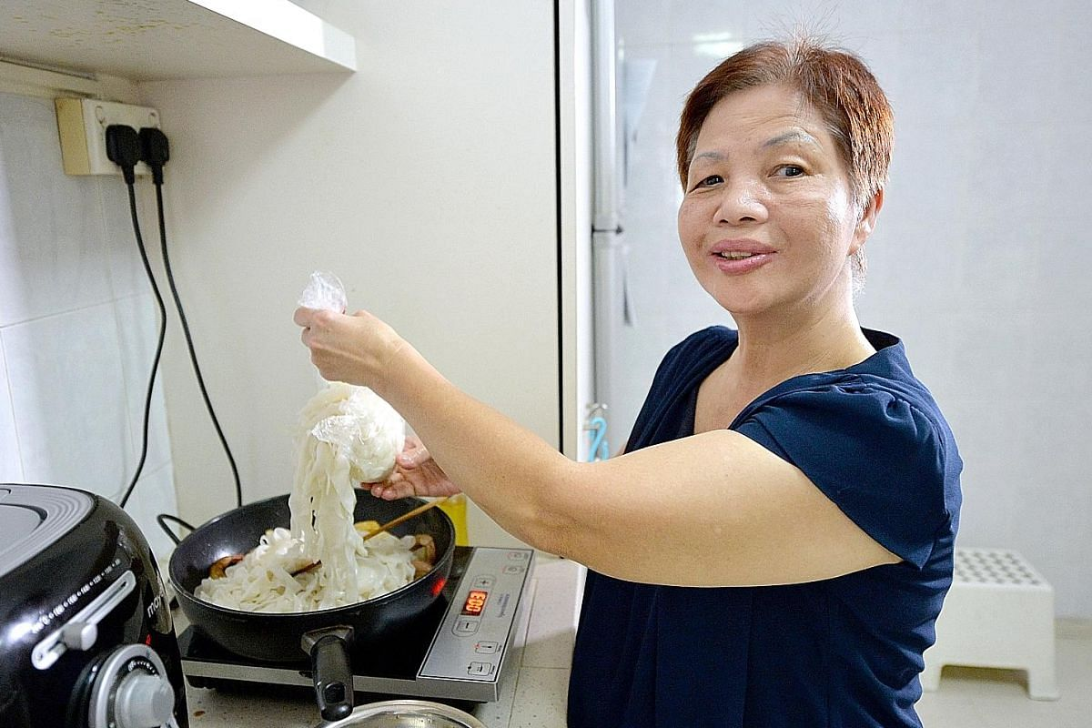 Madam Rosie Wong stir-frying kway teow using her talking induction hob, which vocalises its various functions and temperature settings.