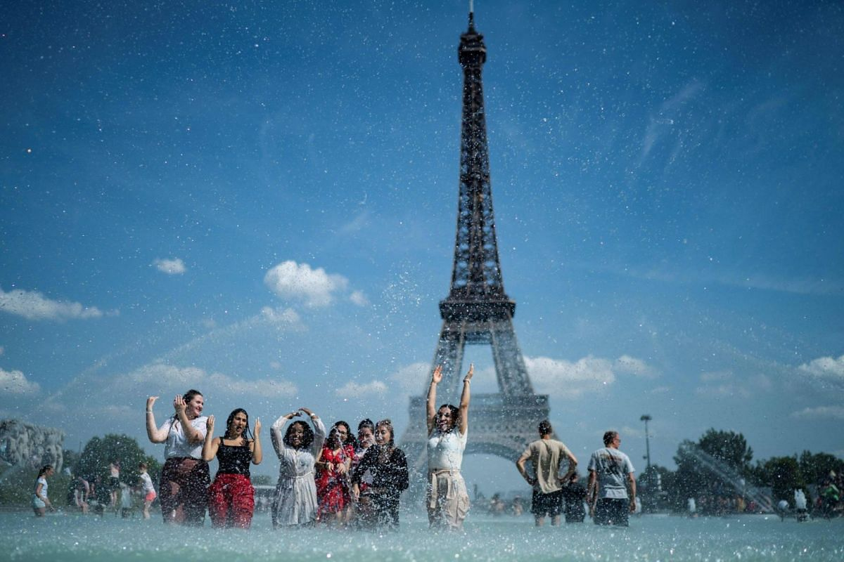 People cool themselves down in the fountain of the Trocadero esplanade in Paris with the Eiffel Tower in the background on June 25, 2019.