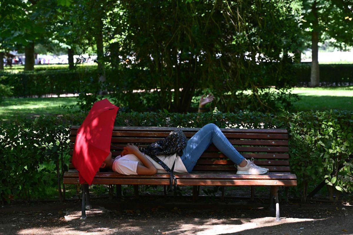 A woman rests at the Retiro Park in downtown Madrid, on a warm summer day on June 25, 2019.
