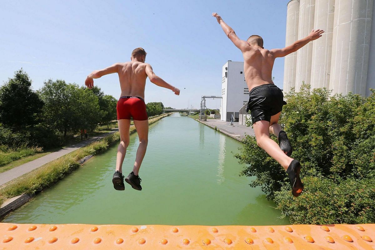 Boys jump into the canal near Reims, northeastern France, as temperatures soar on June 25, 2019.