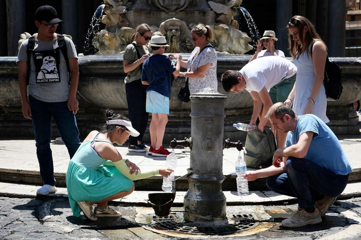 Tourists drink and fill their bottle from a public fountain to refresh themselves during an unusually early summer heatwave on June 24, 2019.