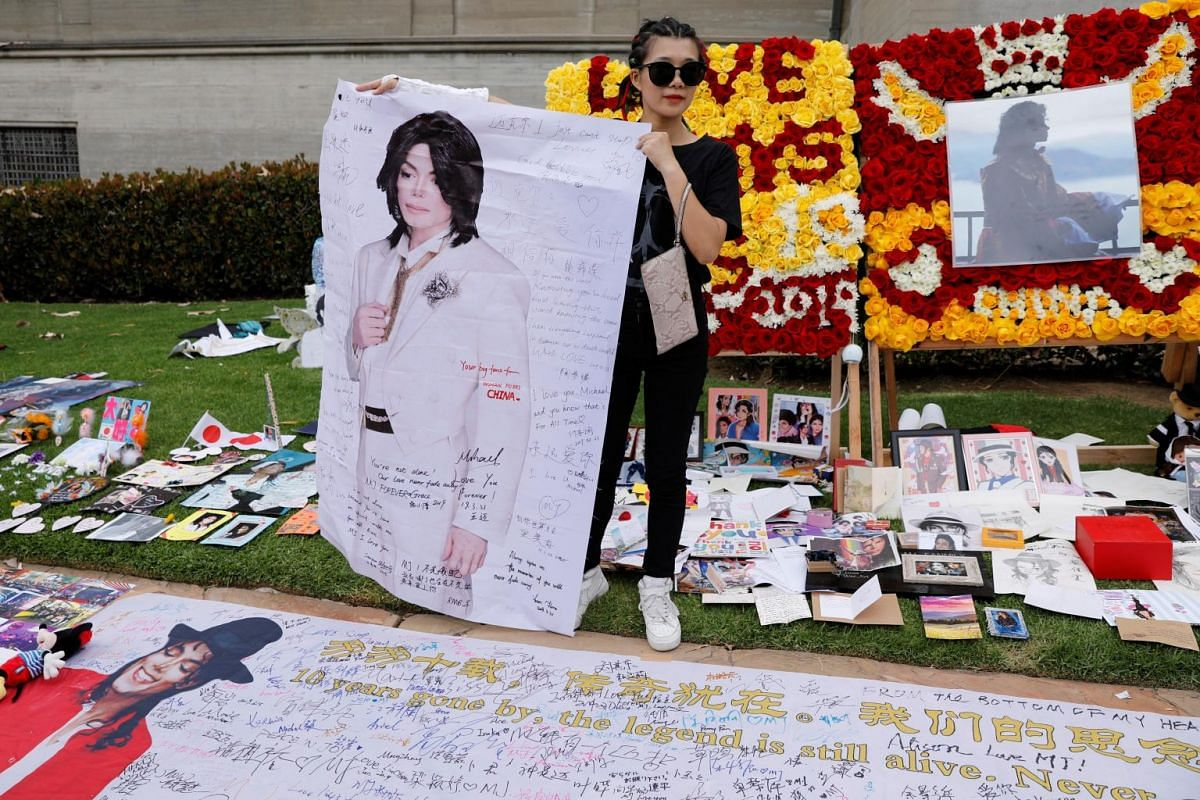 A Chinese fan with a Michael Jackson poster at the Forest Lawn Cemetery.