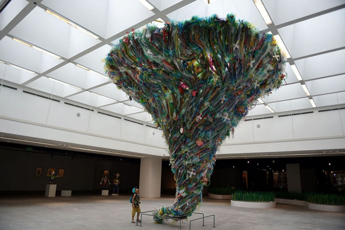 """A boy looks up at the installation entitled """"Tornado by plastic waste"""" by artists from the social enterprise To He at the exhibition """"Plastics Planet"""" in Hanoi on June 27, 2019. PHOTO: AFP"""