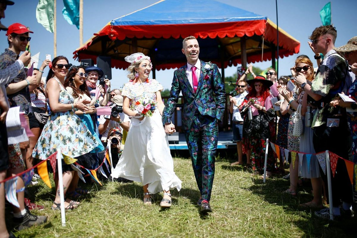 Newlyweds Sarah Adney and Jack Watney celebrate after getting married during the Glastonbury Festival at the Worthy farm in Britain on June 27, 2019.