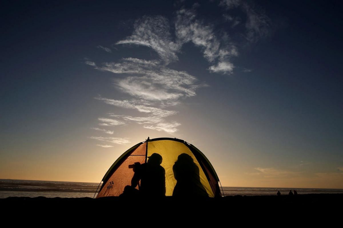 A man taking a picture inside his tent during sunset at a beach in La Serena, Chile, on June 30, 2019.