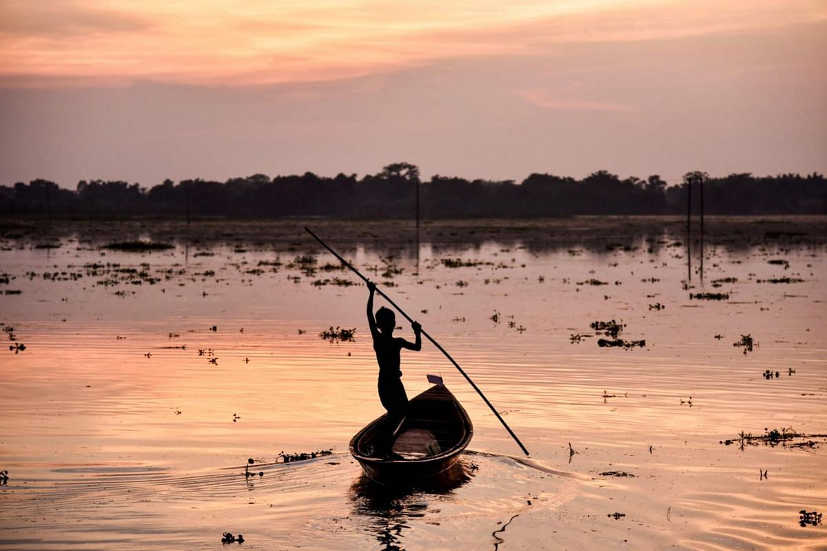 A boy paddles a boat on a paddy field at the flood-affected Kayakuchi village in Barpeta district of Assam state, India, on June 30, 2019.