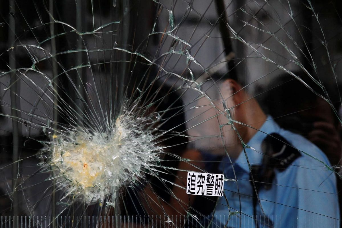 A policeman walks past broken glass at Hong Kong's Legislative Council, a day after protesters broke into the building, on July 2, 2019.