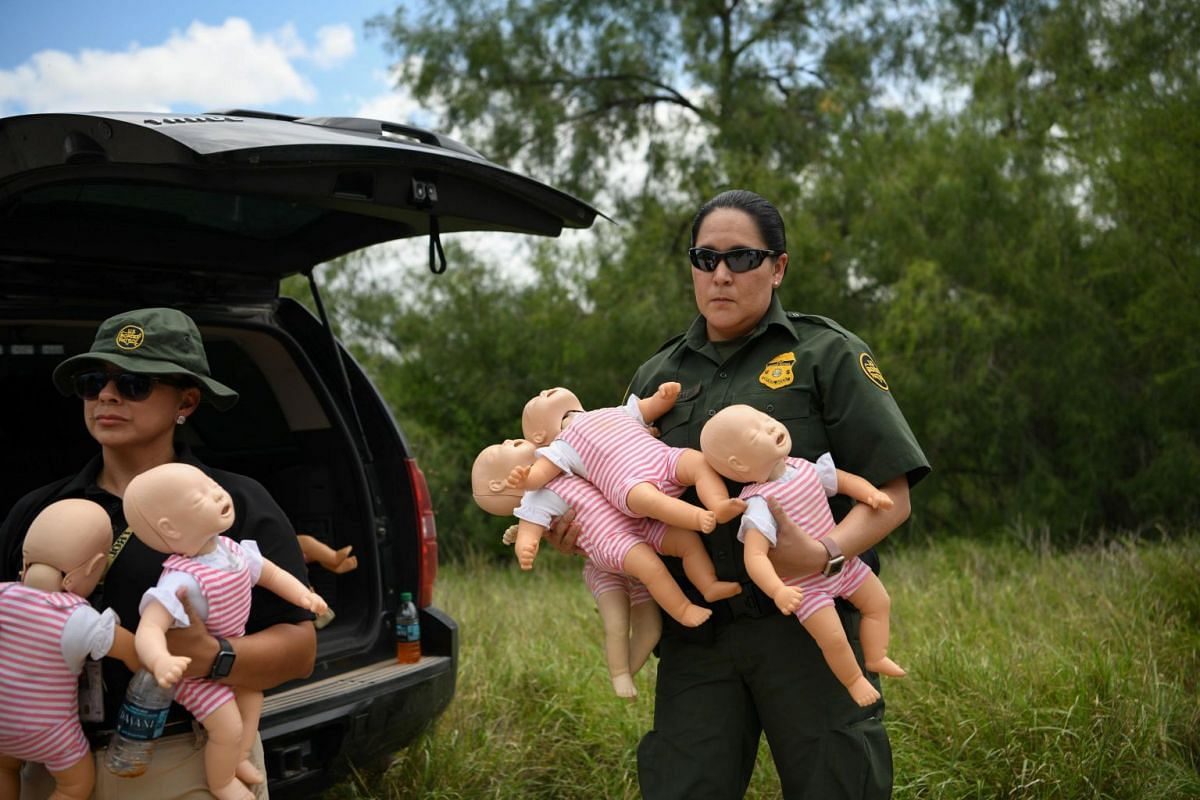A US Border Patrol agent holds infant dolls in preparation for a demonstration during a media event at the US-Mexico border in Mission, Texas, on July 1, 2019.