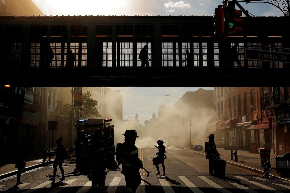 Pedestrians walk past a manhole fire in the Brooklyn borough of New York, on July 1, 2019.