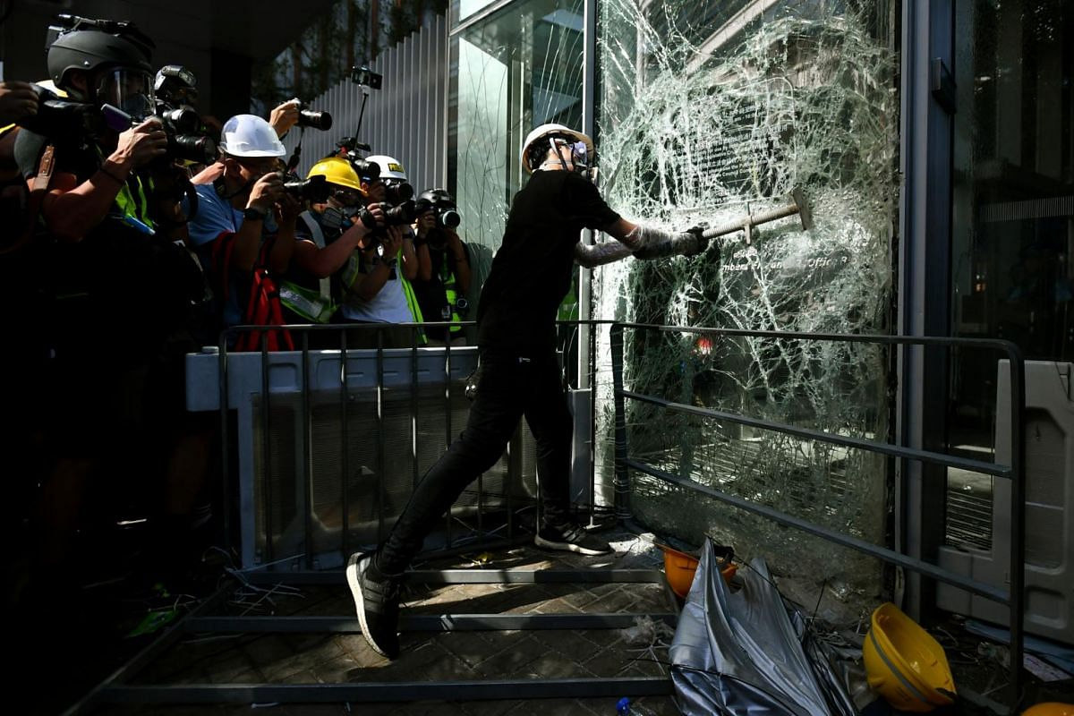 Protesters protect themselves with shields and umbrellas from pepper spray used against them by the police as they try to break a glass panel of the Legislative Council in Hong Kong on July 1, 2019.