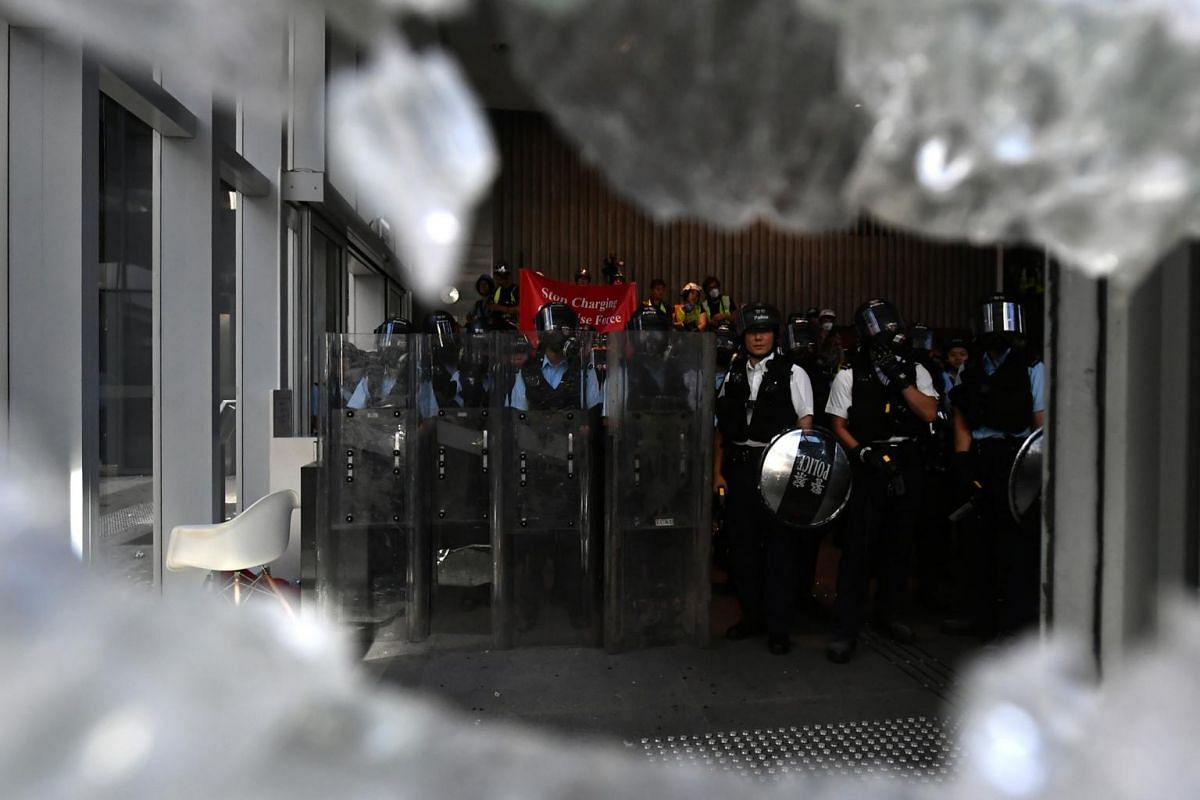 Police standing guard inside the Legislative Council as protesters try to break a glass panel of the building, in Hong Kong on July 1, 2019.
