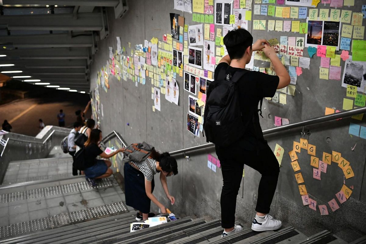 People removing the post-it notes with people's written messages on the Lennon Wall at the Central Government Complex, on July 2, 2019.