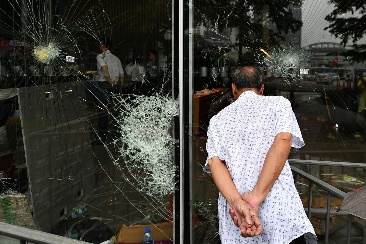 A man looking through the damaged glass panels of the Legislative Council Complex, on July 2, 2019.