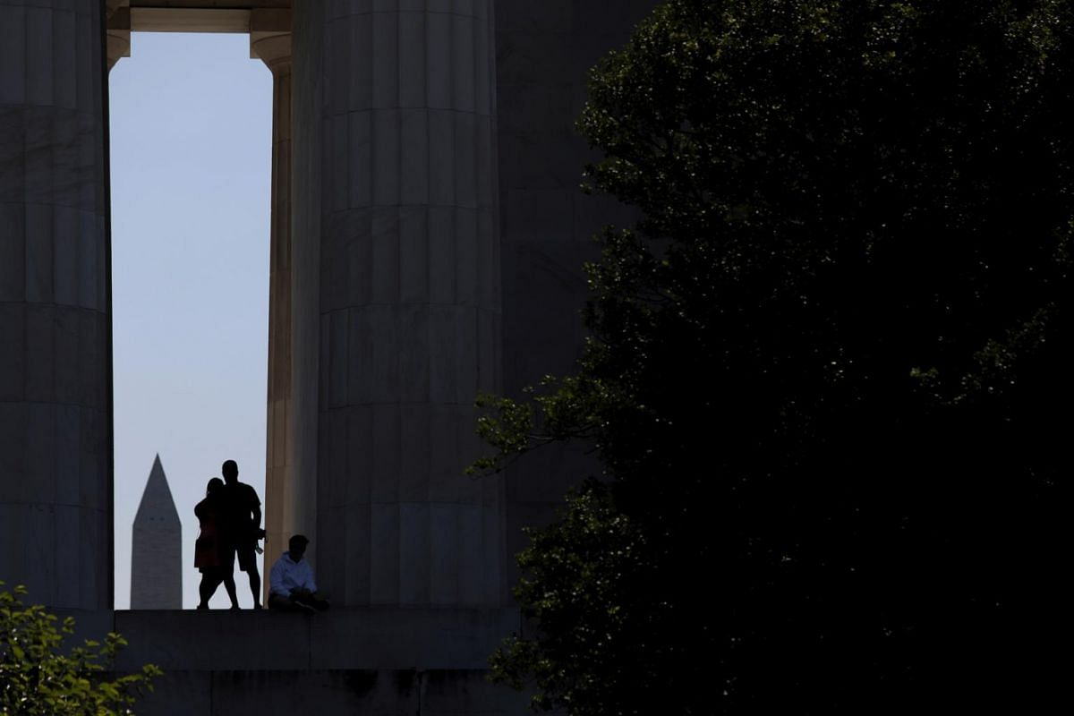 The Washington Monument is seen eclipsed in the background as visitors walk along the west side of the Lincoln Memorial in Washington, on July 3, 2019.