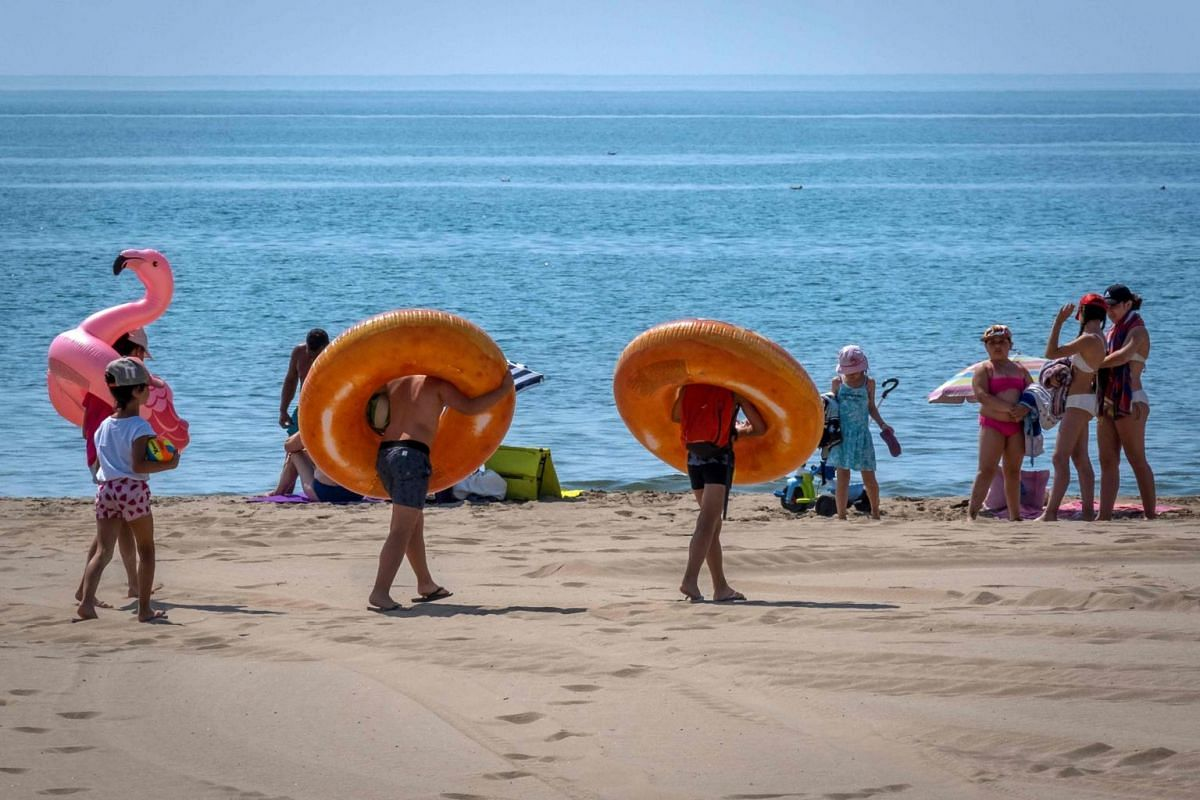 Children walk on the beach with rubber rings around their necks in Narbonne-Plage, France, on July 3, 2019.