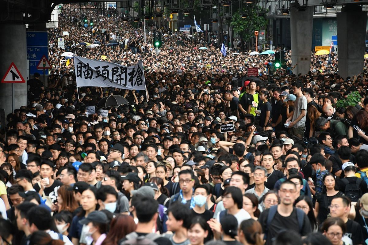 Protesters marching  near Hong Kong's West Kowloon station, which has a rail link that takes travellers as far away as Beijing on the mainland, July 7, 2019. PHOTO: THE STRAITS TIMES/CHONG JUN LIANG