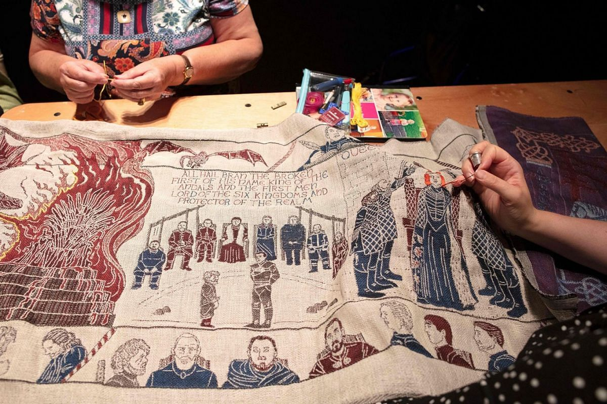 Embroiderers work on the final section of a tapestry depicting the hit television series Game of Thrones at the Ulster Museum in Belfast on July 5, 2019. PHOTO: AFP