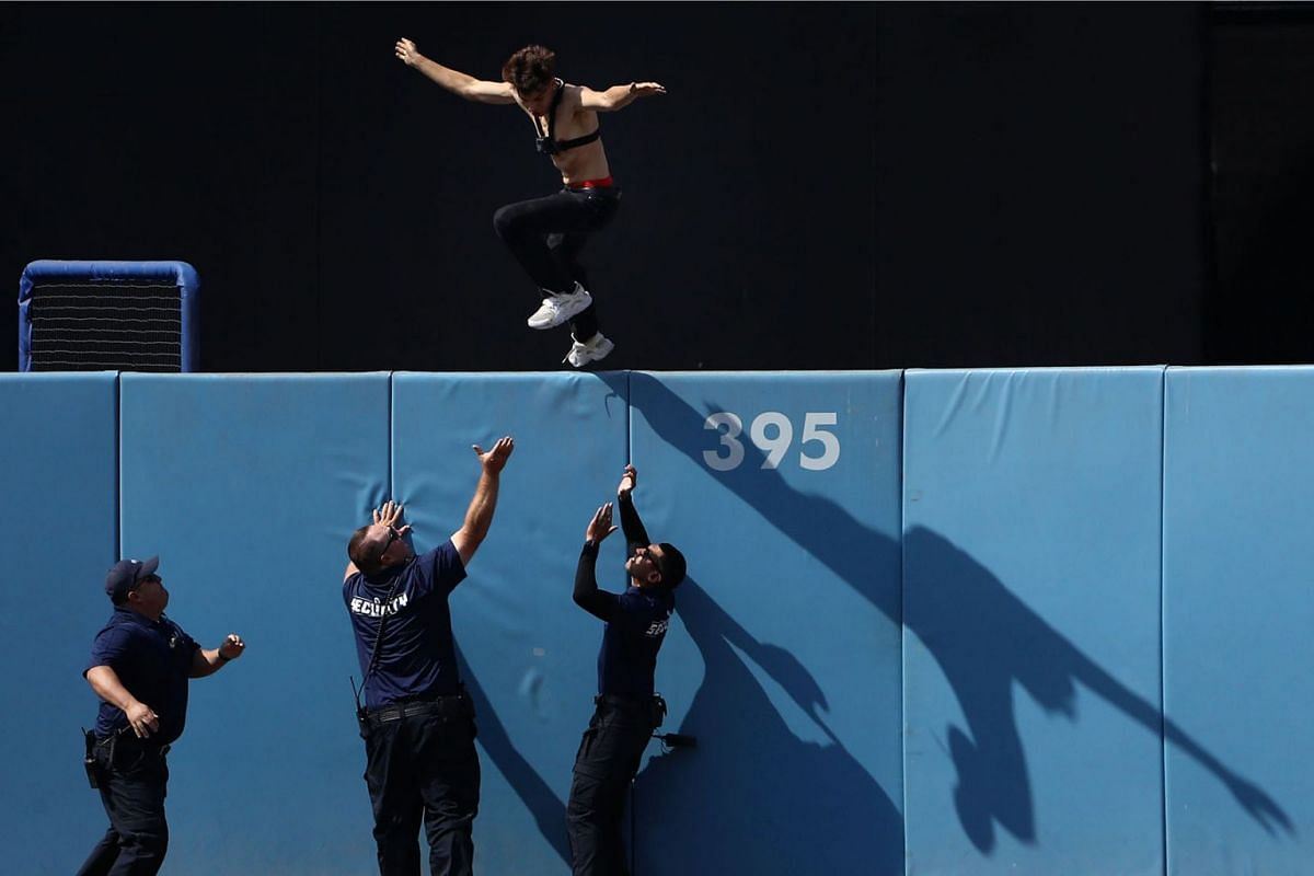 A fan jumps off the center field fence as stadium security guards await him below during the ninth inning of a MLB game between the San Diego Padres and the Los Angeles Dodgers at Dodger Stadium on July 7, 2019 in Los Angeles, California. PHOTO: GETT