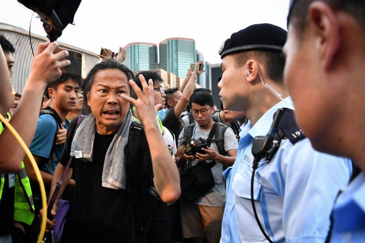 """Protesters confronting policemen after they escorted a man labelled by the crowd as a """"fake reporter"""" to safety."""