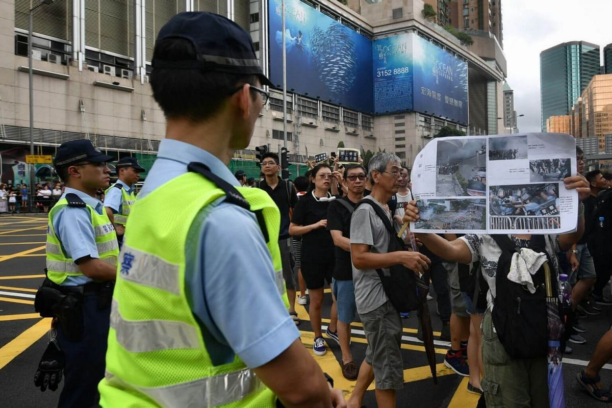 A woman confronts a policeman with posters depicting police brutality.