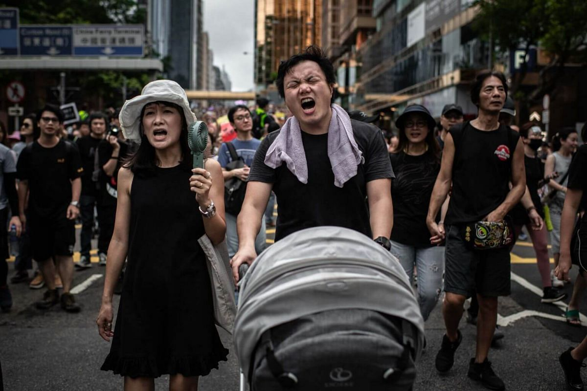 Protesters shout slogans while pushing a baby trolley during the demonstration in Hong Kong, on July 7, 2019.