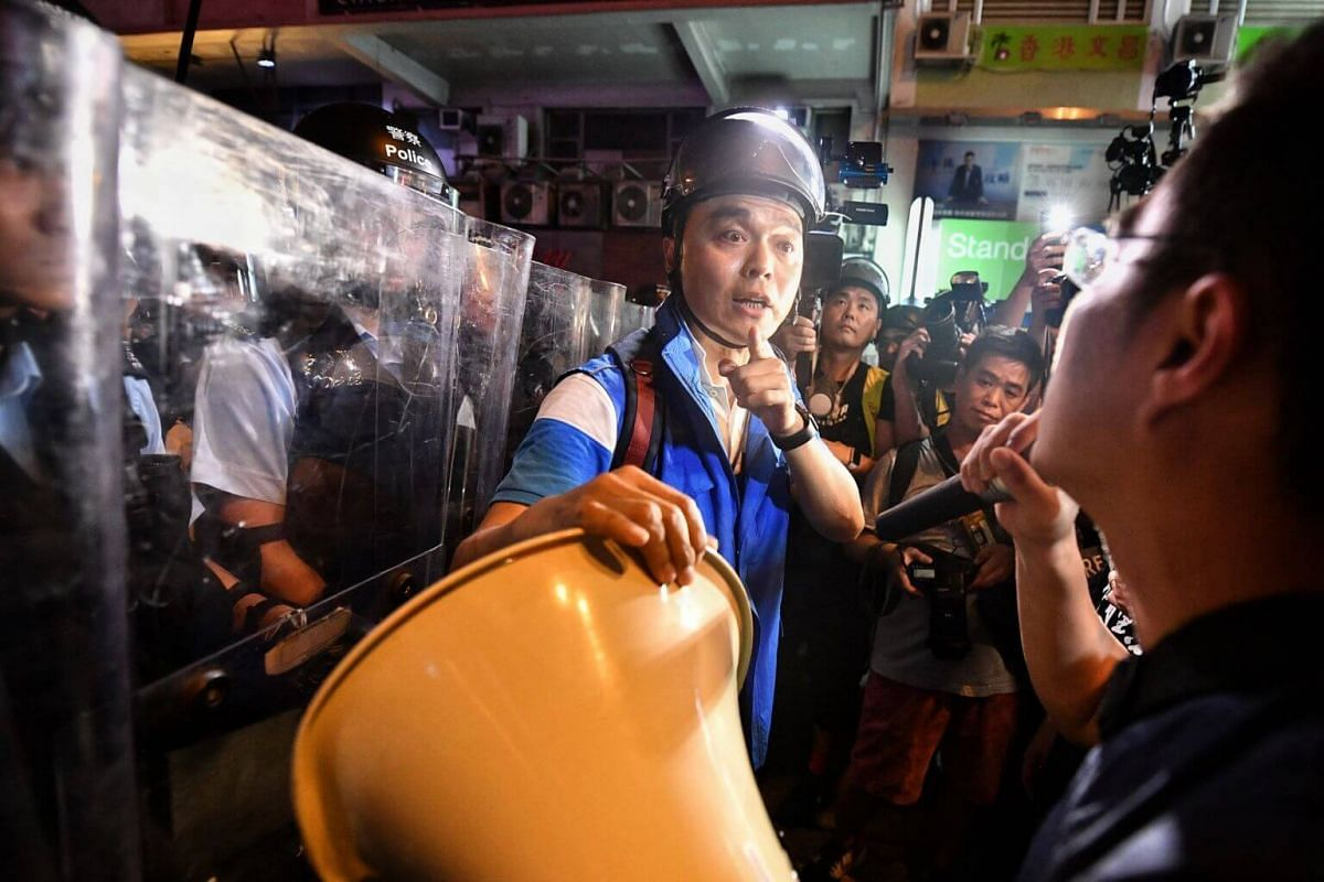 A police officer warns legislative member Au Nok-hin not to aim the loud-hailer at his ear during a confrontation in Mong Kok, on July 7, 2019.