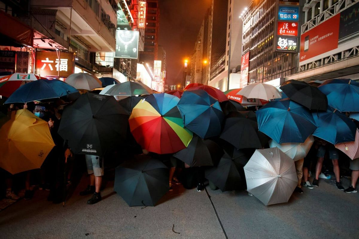 Anti-extradition bill protesters hold umbrellas as they face riot police after a march at Mong Kok, on July 7, 2019.