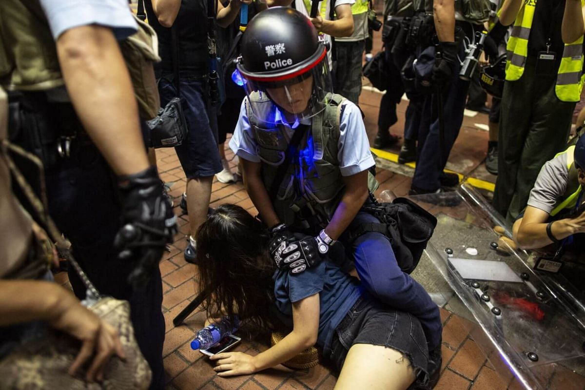 A riot police officer detains anti-extradition bill protester after a march in Hong Kong, on July 7, 2019.
