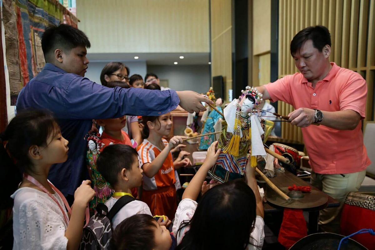 Ang Wei Hao (left) and his uncle introducing Teochew puppets to young audience during the Cultural Extravaganza 2019 at Singapore Chinese Cultural Centre, on June 9, 2019.