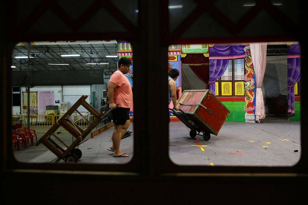 Madam Tina Quek's sons Ang Wei Hao (left) and Wei Li unloading props from the lorry backstage at Lorong Koo Chye Sheng Hong Temple, on June 27, 2019.