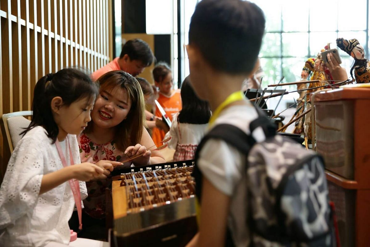 Ms Christine Ang introducing the yang qin, or Chinese hammered dulcimer, to a young audience member after a puppet performance by Sin Ee Lye Heng during the Cultural Extravaganza 2019 at Singapore Chinese Cultural Centre, on June 9, 2019.